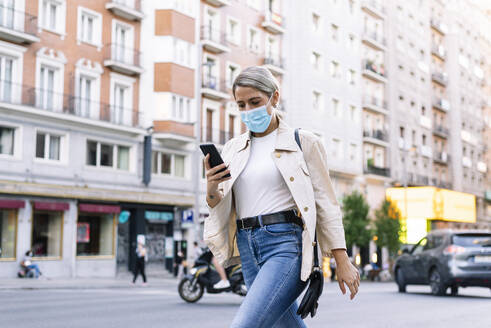 Young woman wearing mask using mobile phone while walking on street in city - JCMF01489