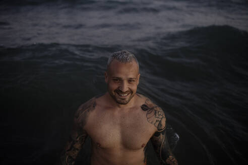 Smiling shirtless mid adult man standing in sea - GMLF00637