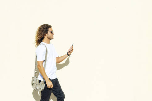 Young man wearing sunglasses using mobile phone while walking by white wall - PGF00028