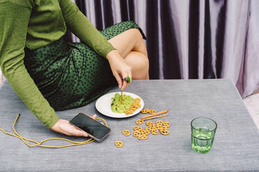 Woman holding smart phone eating guacamole and pretzel while sitting on table at home - ERRF04439