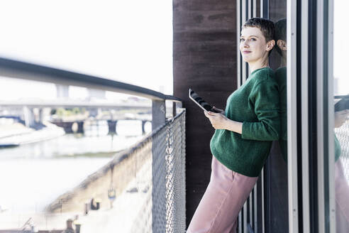 Thoughtful businesswoman with digital tablet standing in balcony at office - UUF21539