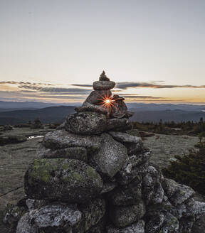 Rock cairn frames setting sun on summit of Baldpate Mountain, Maine - CAVF89397