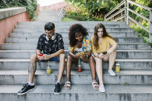 Young friends text messaging on smart phone while sitting on steps in park - XLGF00571