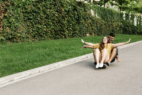 Friends enjoying riding on skateboard with arms outstretched in park - XLGF00577