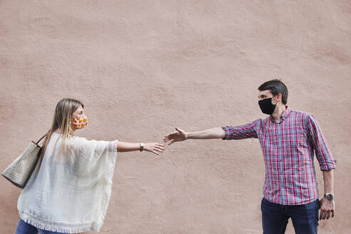 Couple keeping social distance while standing against wall - SASF00111