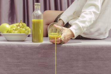 Close-up of woman throwing green juice while sitting on table at home - ERRF04446