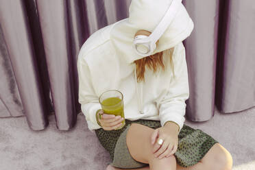 Woman with green juice listening music over headphones while sitting at home - ERRF04449