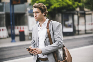 Man with bag using mobile phone while standing in city - UUF21565