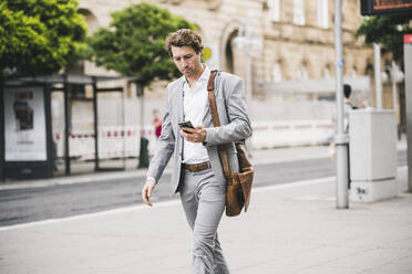 Businessman using mobile phone while walking in city - UUF21568