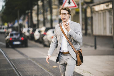 Man wearing eyeglasses talking on mobile phone while walking at tramway in city - UUF21577