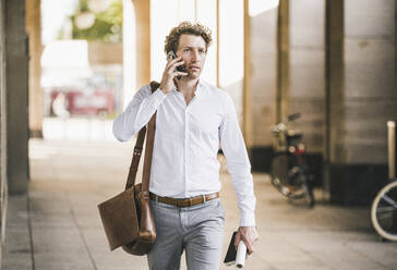 Man talking on mobile phone while walking at building in city - UUF21580