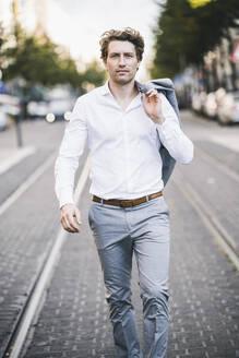 Confident businessman walking with jacket on shoulder city - UUF21586