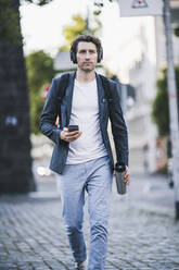 Businessman with headphone using mobile phone while walking on street in city - UUF21592