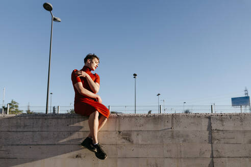 Non-binary man sitting on surrounding wall against clear sky - TCEF01089