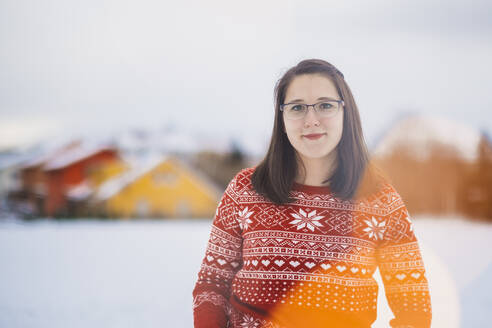 Smiling young woman standing on snow covered land against sky - JSCF00157