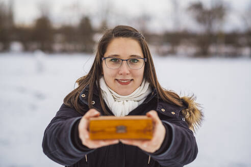 Close-up of smiling young woman holding Christmas present while standing outdoors during winter - JSCF00160