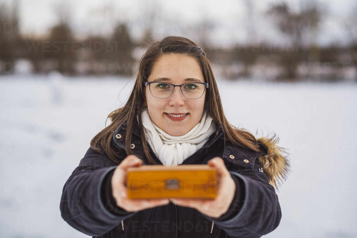 Close-up of smiling young woman holding Christmas present while standing outdoors during winter - JSCF00160 - Jonathan Schöps/Westend61