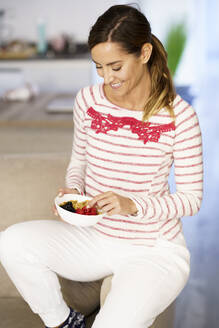 Smiling woman holding bowl of nut and berries while sitting at home - JSMF01710