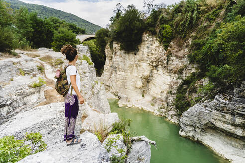 Woman with backpack admiring view while standing on mountain at Marmitte Dei Giganti, Marche, Italy - MCVF00622