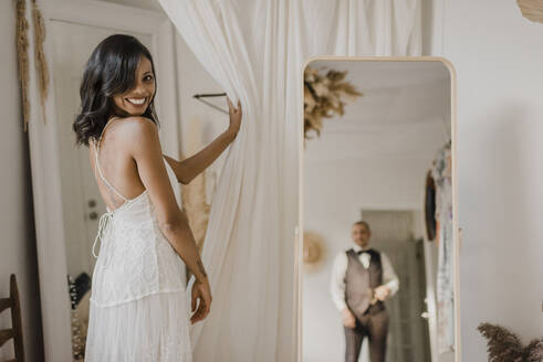 Reflection of bridegroom in mirror while bride looking over shoulder at home - SMSF00322