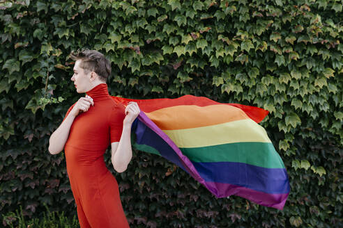 Non-binary person in red dress holding rainbow flag while standing against ivy wall - TCEF01159