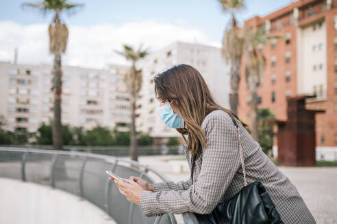 Young woman wearing face mask while using smart phone leaning on railing in city - GRCF00394