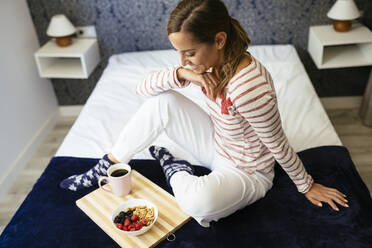 Smiling woman looking at food and coffee while sitting on bed at home - JSMF01750