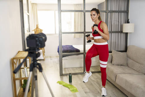 Woman exercising with dumbbell in front of camera at home - JSMF01753