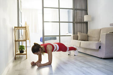Sportswoman doing plank on floor at home - JSMF01756