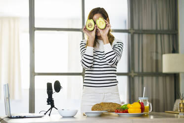 Woman hiding face with fruit during online tutorial at home - JSMF01762
