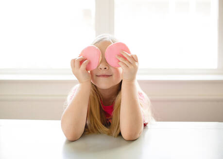Cute blond girl holding pink frosted sugar cookies over eyes - CAVF89505
