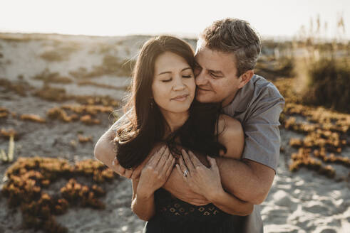 Mid-40's husband embraces beautiful wife with sand dune in background - CAVF89559