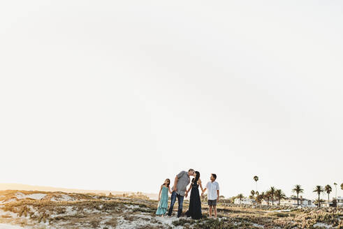 Family holding hands at beach as dad kisses mom - CAVF89571