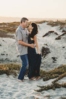 Loving embrace between barefoot mid-40's couple standing in sand - CAVF89577