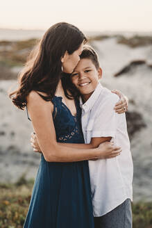 Beautiful mom tenderly embracing handsome preteen son at the beach - CAVF89583