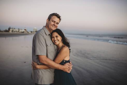 Happy mid-40's couple embracing on ocean beach - CAVF89586