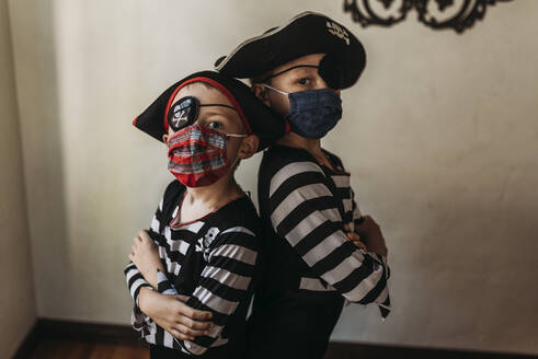 School age brothers dressed as pirates with face masks on - CAVF89598