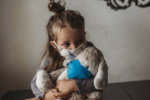 Close up of young girl with mask on kissing masked stuffed animal - CAVF89607