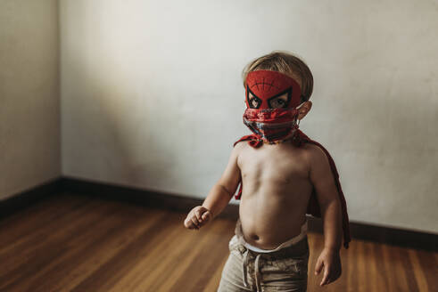 Toddler boy walking in Halloween costume and face mask - CAVF89613