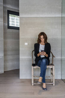 Woman using mobile phone while sitting on chair against wall at office - DLTSF01230