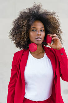 Curly hair woman with headphones standing against wall - MGIF00976