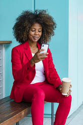 Woman holding disposable coffee cup while using smart phone sitting on bench - MGIF00997