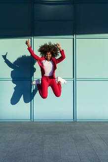 Cheerful woman with hand raised jumping against wall - MGIF01000