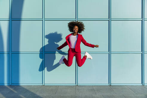 Smiling woman jumping against blue wall on sunny day - MGIF01003