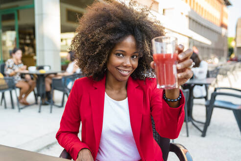 Mid adult woman holding juice glass while sitting at sidewalk cafe - MGIF01012