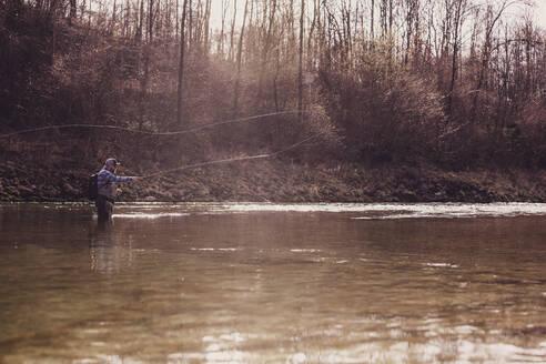 Fly fisherman throwing fishing reel in river during sunset - DHEF00416
