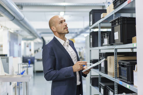 Mature male professional with digital tablet looking at containers on rack in industry - MOEF03277