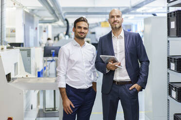 Confident mature businessman holding digital tablet while standing by young male engineer at factory - MOEF03280