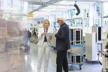 Confident businesswoman discussing over digital tablet with senior businessman in factory - MOEF03301
