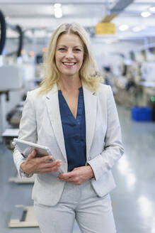 Smiling mature blond businesswoman holding digital tablet while standing at illuminated industry - MOEF03304